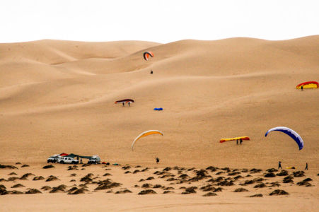 These guys are hang-gliding down from the dunes.